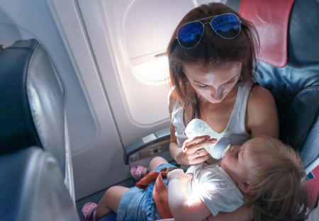Young mother feeding her small daughter from bottle on airplane Stock Photo