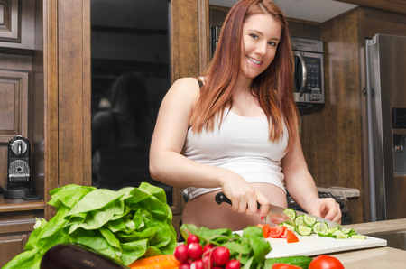 Pregnant woman cutting Cucumber for salad Stock Photo