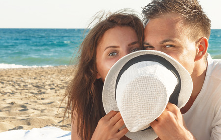 Close up of handsome couple happy hiding behind hat  while relaxing on beach - copyspace
