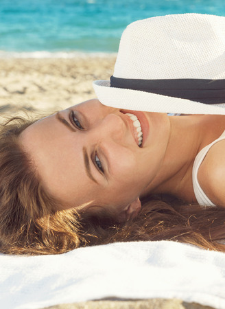 Closeup portrait of a beautiful woman lying and smiling with the sun hat while  on the beach