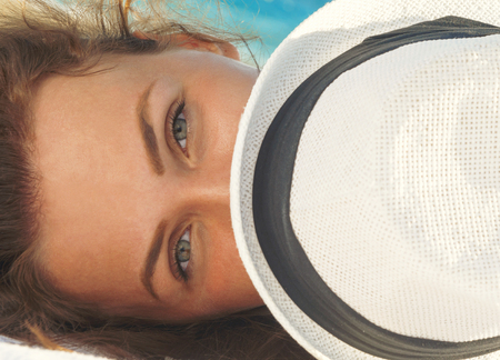 Closeup portrait of gorgeous woman cover the face a sun hat while lying on the beach