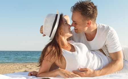 An attractive young couple enjoying a beach getaway - Copyspace