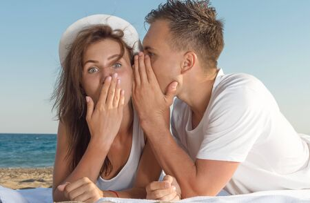 A young man whispering a secret in his girlfriends ear Stock Photo