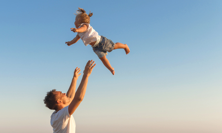A Father swinging his  daughter  in the air against a sky background, Copyspace