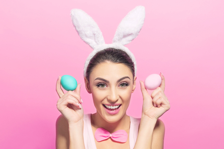 Studio shot of a excited young woman wearing bunny ears and holding a of Easter eggs on pink background