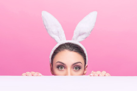 Studio shot of a surprised  bunny-woman wearing bunny ears and peeking over a surface