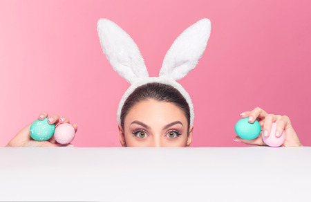 Studio shot of a young woman wearing bunny ears peeking over a surface and holding easter eggs Stock Photo