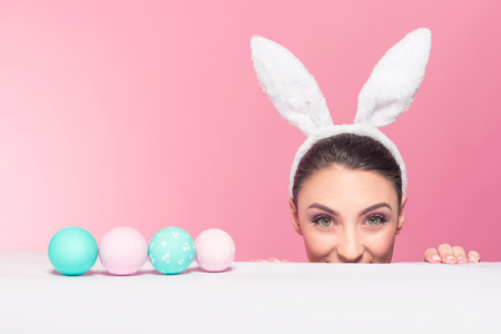 Studio shot of a young woman wearing bunny ears and peeking over a surface, copy space