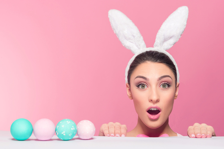 Surprised  young woman wearing bunny ears while peeked over surface