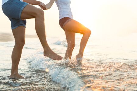 Cropped shot of a couple splashing in the water at the beach