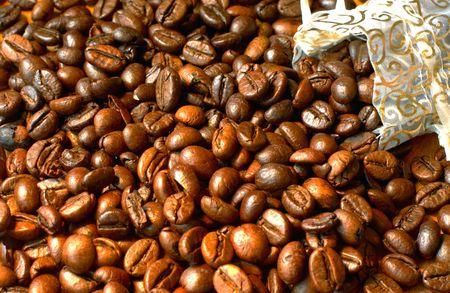 Fresh roasted coffee beans in a gold silk bag
