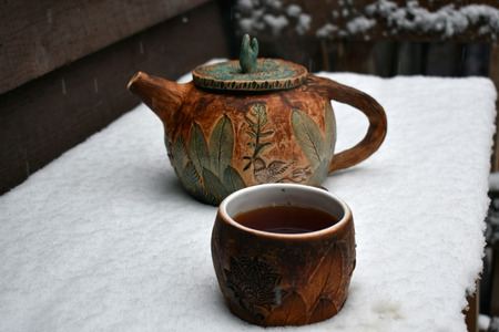 Artistic hand-made pottery ceramic teapot and cup in the first snow with steaming black tea.