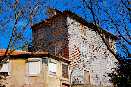 Porto (Portugal) buildings with the typical colorful facades and the scale tiles falling apart