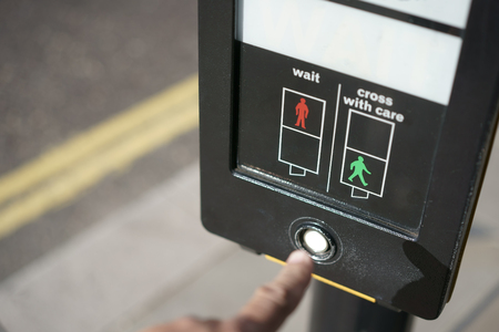Humans finger presses the traffic lights button