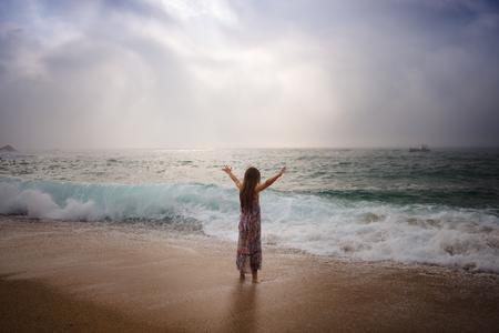 Girl with long hair standing by sea Zdjęcie Seryjne