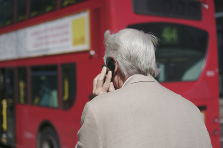 Old man going near red bus talking on phone. Zdjęcie Seryjne