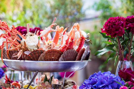 Seafood dish and flowers on restaurant table