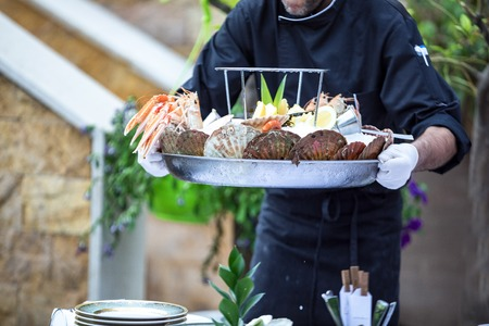 Waiter serves fresh seafood platter