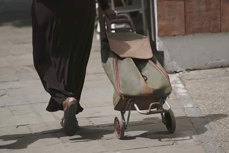 Woman goes with bag on wheels