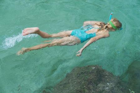 Chica rubia en traje de baño azul, máscara y aletas flota bajo el agua. Los niños descansan. Reglas de natación Foto de archivo