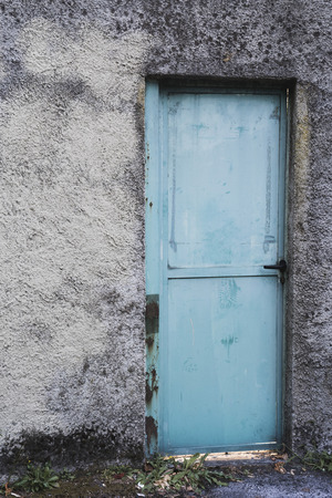 old house concrete wall with blue door