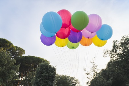 Colorful helium balloons on sky background, summer party concept