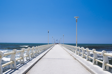 Long pier heading to the sea, in a sunny day with blue sky. Zdjęcie Seryjne