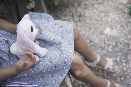 Child girl with a soft toy on his lap outdoor on a summer day. Conceptual image of child or adolescent loneliness Zdjęcie Seryjne