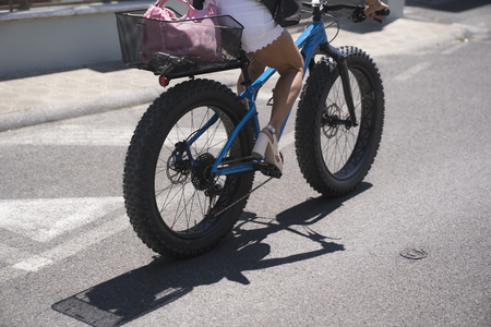 Riding a fatbike with high heel shoes. Female person riding a bicycle in the city. Zdjęcie Seryjne