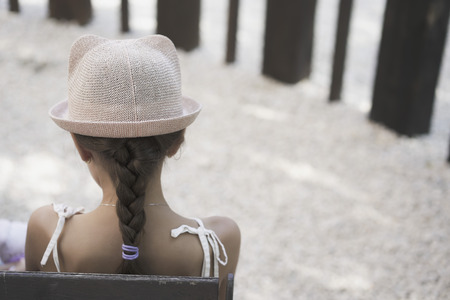 Back view of tennager girl in a stylish hat. Beautiful brunette teenager girl with long hair in bowler hat and a sammer dress.