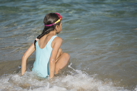 Teenager girl swims in the sea. Girl likes the sea and the beach. Happy summer holiday, summer vacation concept. Summer fun.