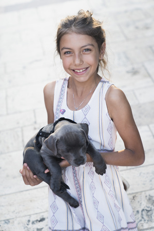 Black puppy playing with a girl