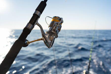 Closeup on fisherman rod on the ocean coast background