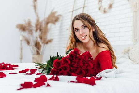 portrait of blonde girl with bouquet of red roses lying on the bed in the room, looking at the camera.