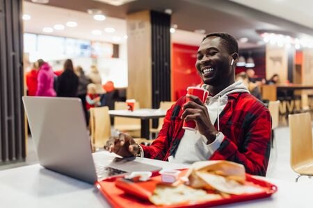 Portrait of positive man, sitting at modern cafe, use laptop while eating fast food and drinking cola