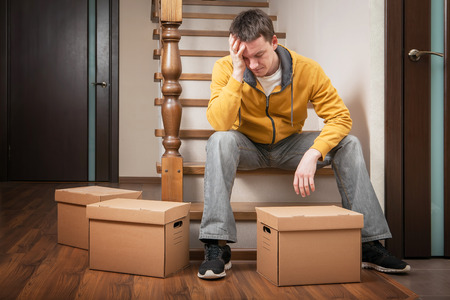 delievery: Moving house. Young man with cardboard boxes on a stairs. Stock Photo