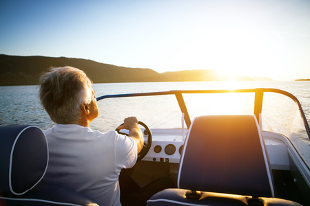 boat: mature man driving speedboat