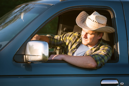 young man in straw hat driving truck