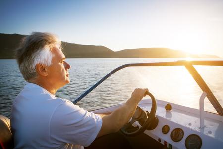 speedboat: mature man driving speedboat
