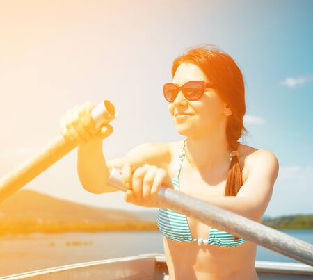 filtered: young woman rows the boat (filtered) Stock Photo