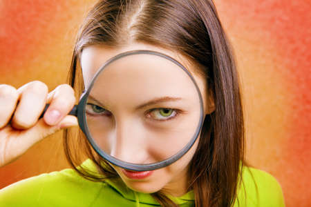 low scale magnification: young woman with magnifying glass Stock Photo