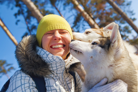 sled dogs: young woman emracing sled dogs
