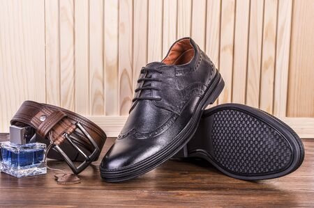 Mens leather shoes with a leather belt and mens perfume. Banco de Imagens
