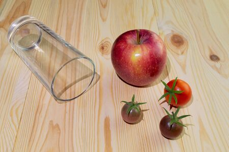 Empty glass for juice from a glass on a wooden background with tomatoes and apple