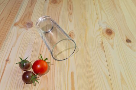 Getting a healthy diet, making fresh juice. Empty glass for juice from a glass on a wooden background with tomatoes and apple