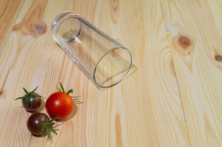 Empty glass for juice from a glass on a wooden background with tomatoes and apple. Getting a healthy diet, making fresh juice.
