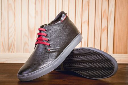 Mens shoes. Leather boots with accessories on a wooden background.