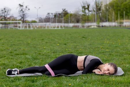 Tired and happy girl after sport training with fitness elastic on green lawn