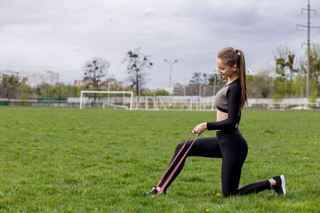 Fitness girl workout with fitness elastic bands in black tracksuit outdoors Stock Photo