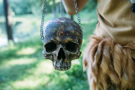 girl holds a skull on a metal chain